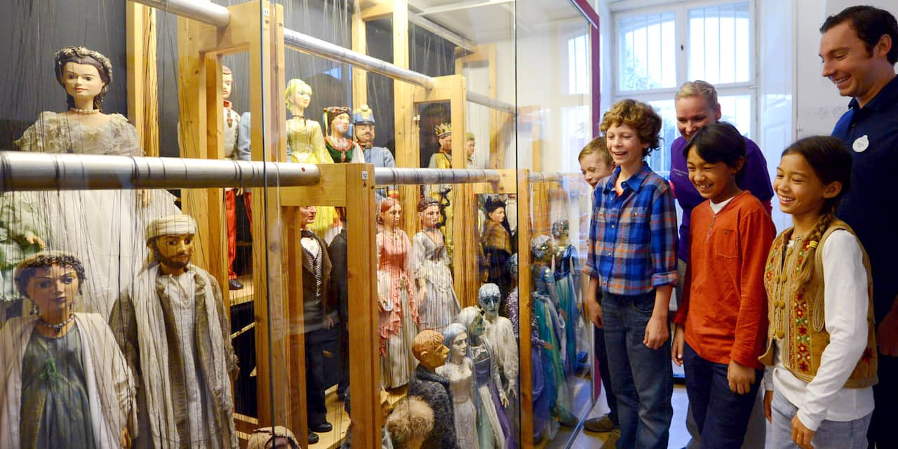 Children look at a collection of marionettes