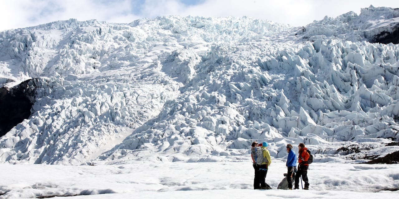 A group of hikers gather at the base of a glacier