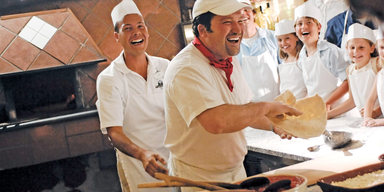 A smiling chef laughs while teaching a group of kids how to make pizza
