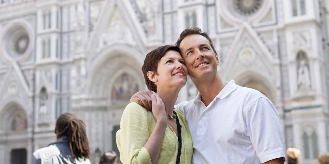 A couple admires the scenery as they sightsee near a cathedral