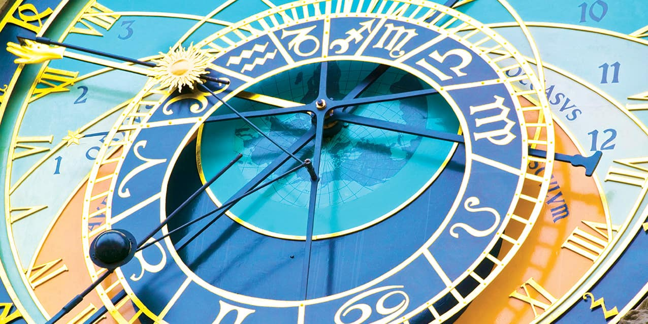 A larhe astronomical clock features roman numerals, zodiac symbols and hands with a sun and a moon