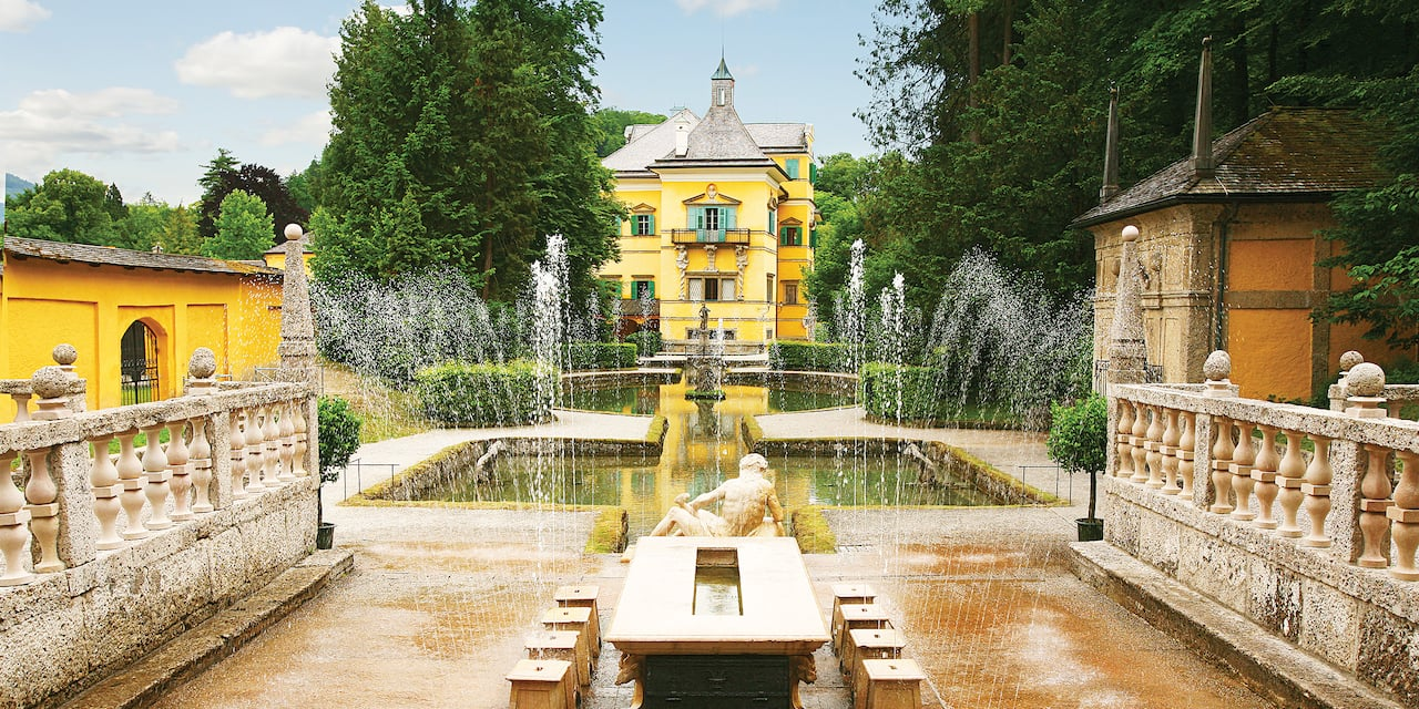 A fountain at Hellbrunn Palace sprays streams of water near a reclining statue