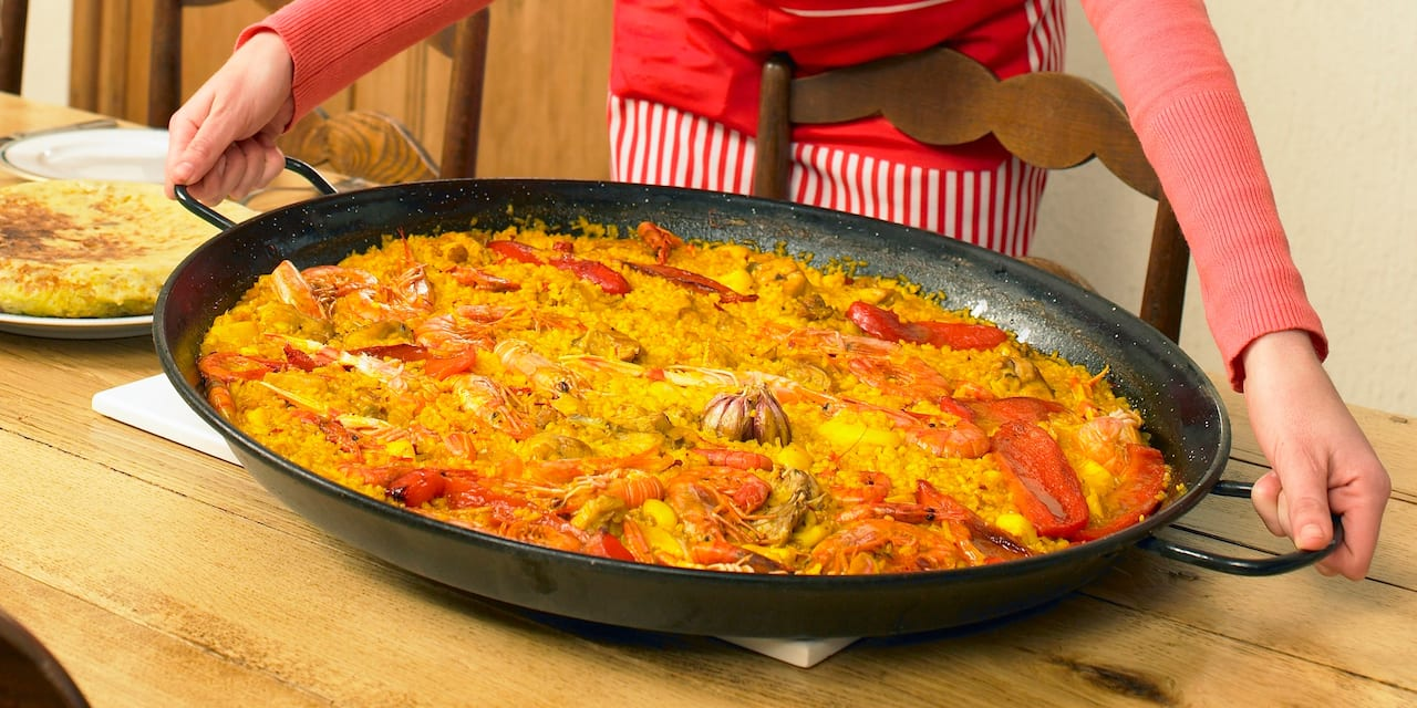 A woman places a large pan of paella on a wooden dinner table