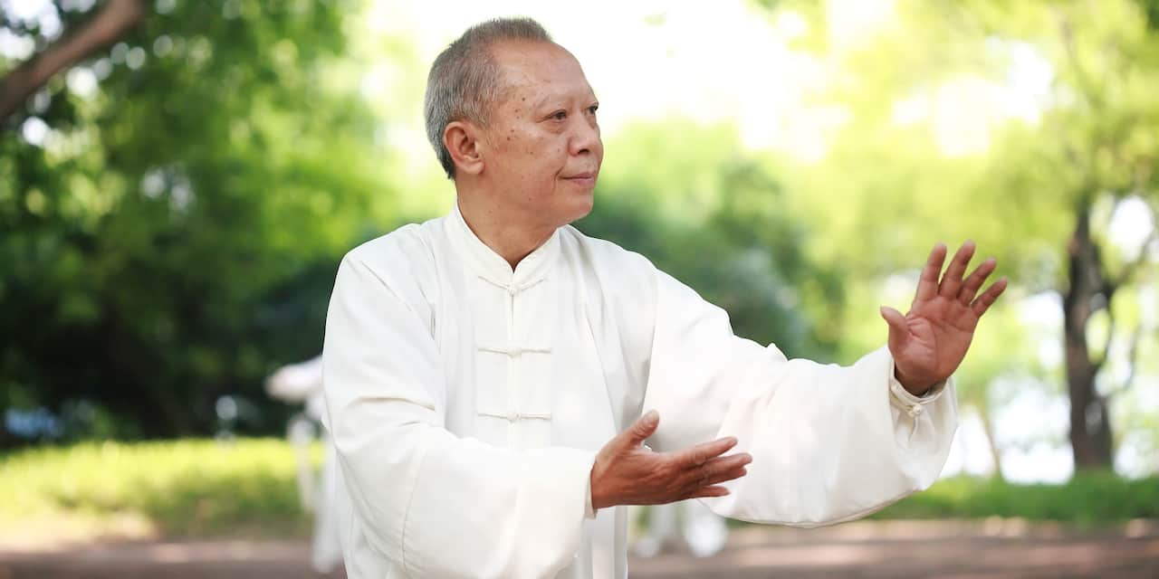 An older man practices Tai Chi in a park