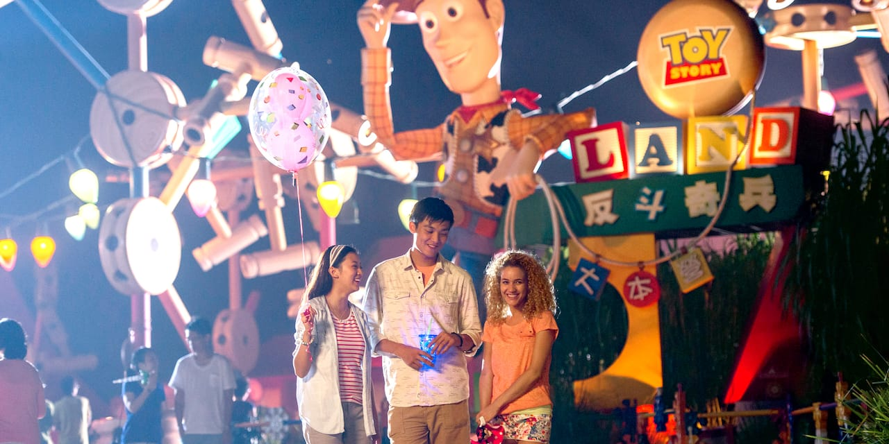 Two teenage girls and a teenage boy stand in front of a Sheriff Woody figure at the entrance to Toy Story Land at Hong Kong Disneyland