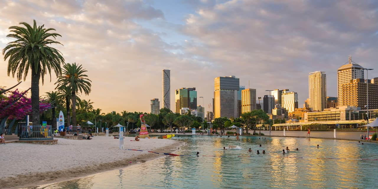 A sandy beach with palm trees on the shores of the Brisbane River near the Brisbane, Australia skyline