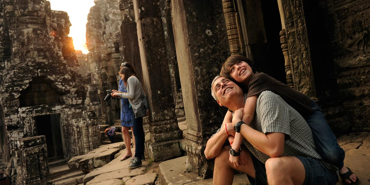 A father and son embrace while sitting in an ancient ruin