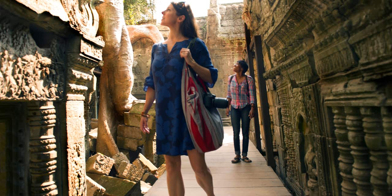 A woman with a purse slung over her shoulder stands on a walkway while looking at a structure in the Angkor Wat Archaeological Park