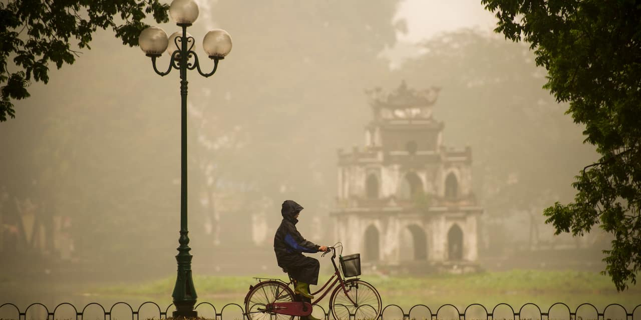 A hooded bicyclist rides past a lamp post on a sidewalk near an old temple in the rain