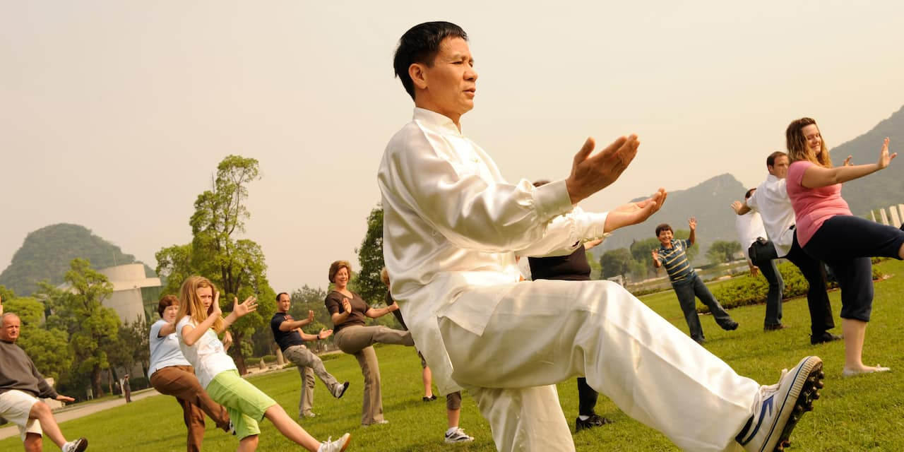 A dozen people practice Tai Chi on a lawn