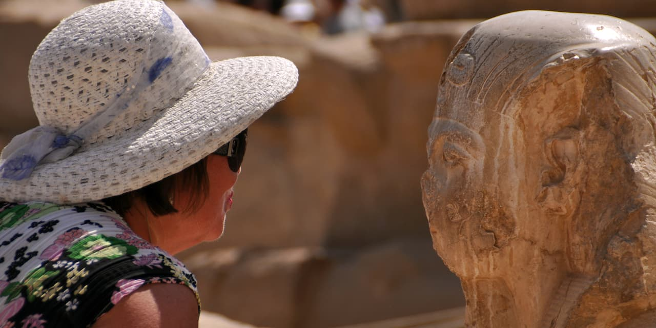 A woman in a hat takes a close-up look at a sculpture in the Valley of the Kings