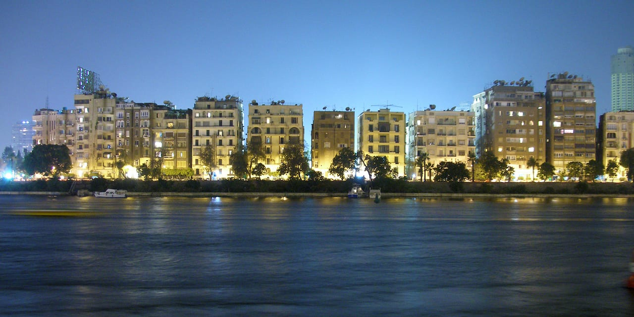 Lit up buildings of the Cairo, Egypt skyline along the Nile River at dusk
