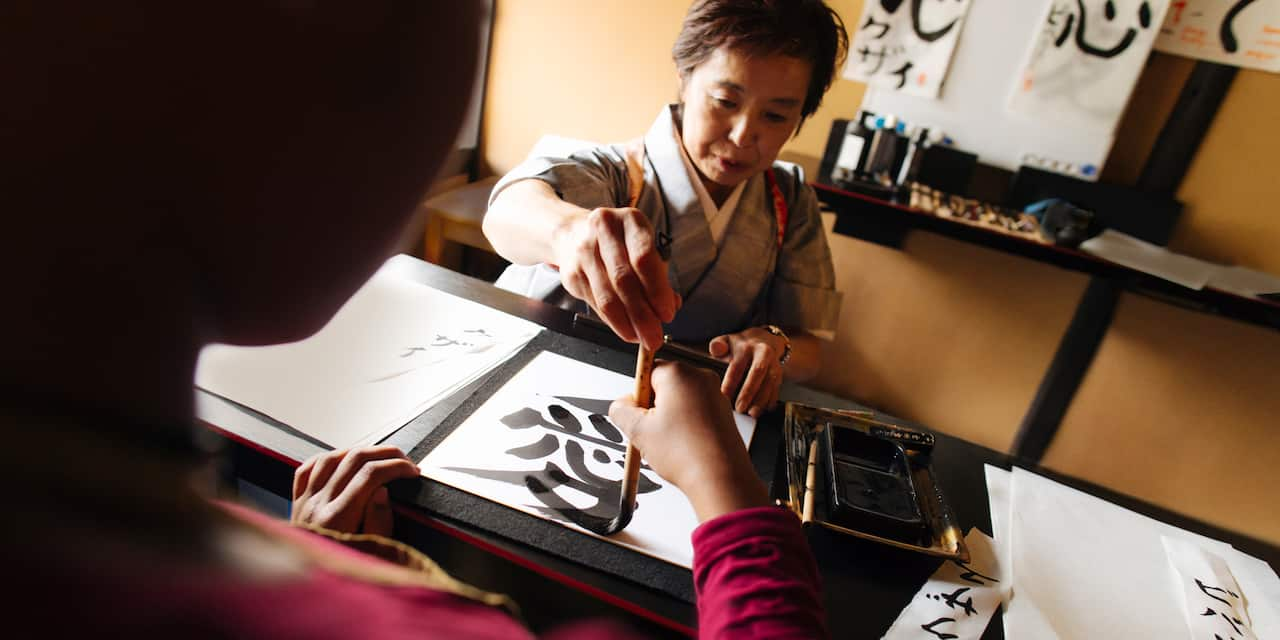 A Japanese woman helps guide the brush of a woman learning calligraphy