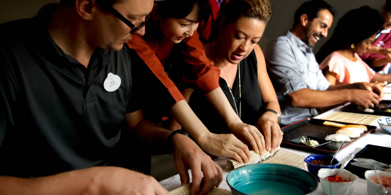 An Adventure Guide and several Adventurers learn to roll sushi from Japanese instructors