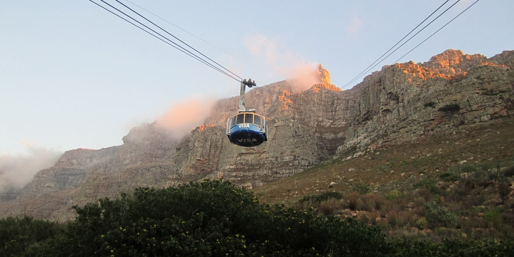 An aerial cable car ascends, heading for the summit of the iconic Table Mountain in South Africa