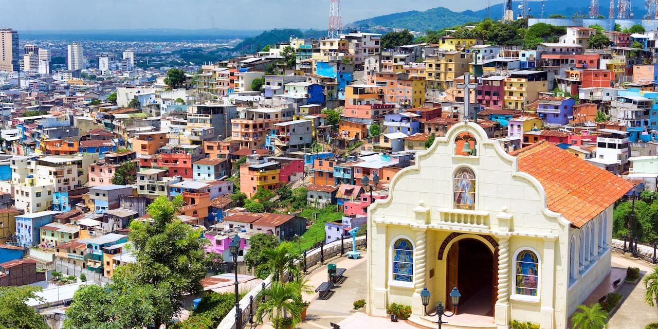 A church sits atop a hill overlooking the tiered buildings of Guayaquil, Ecuador that is spread out to the city skyline and a backdrop of mountains in the distance