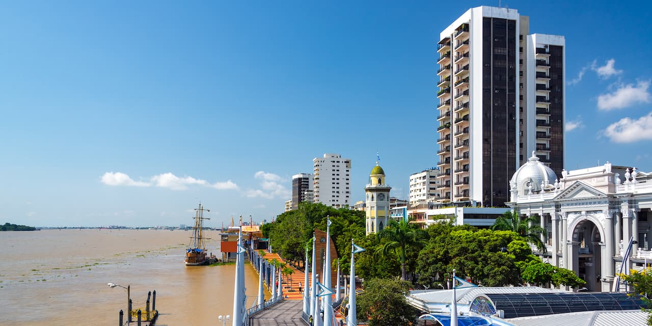 A boat is docked along a boardwalk that stretches between the Guayas River and a building lined street with several high rises and domed buildings