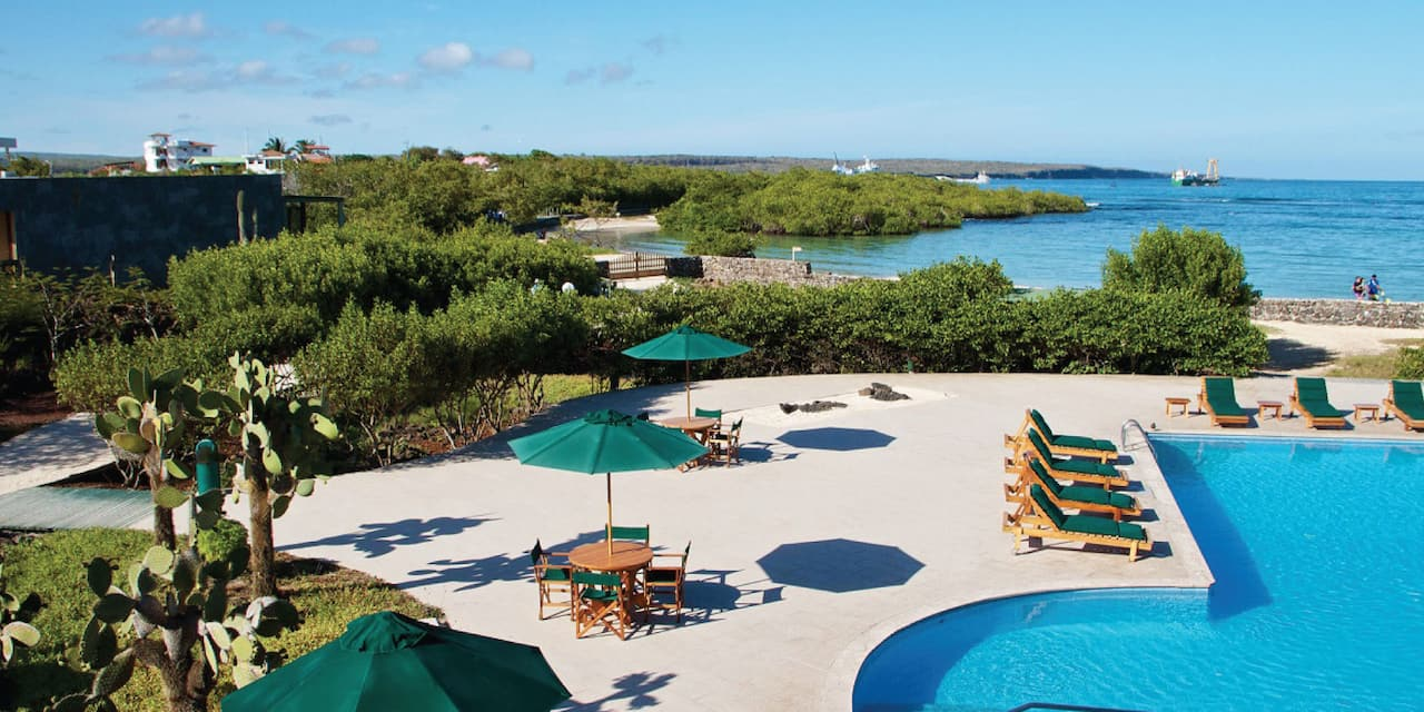 A patio lying between a pool and an ocean, with outdoor recliners and tables with umbrellas