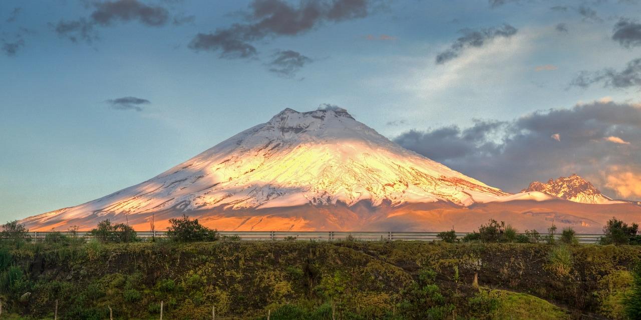Cotopaxi volcano looms high above a lush, tree filled area near Quito, Ecuador
