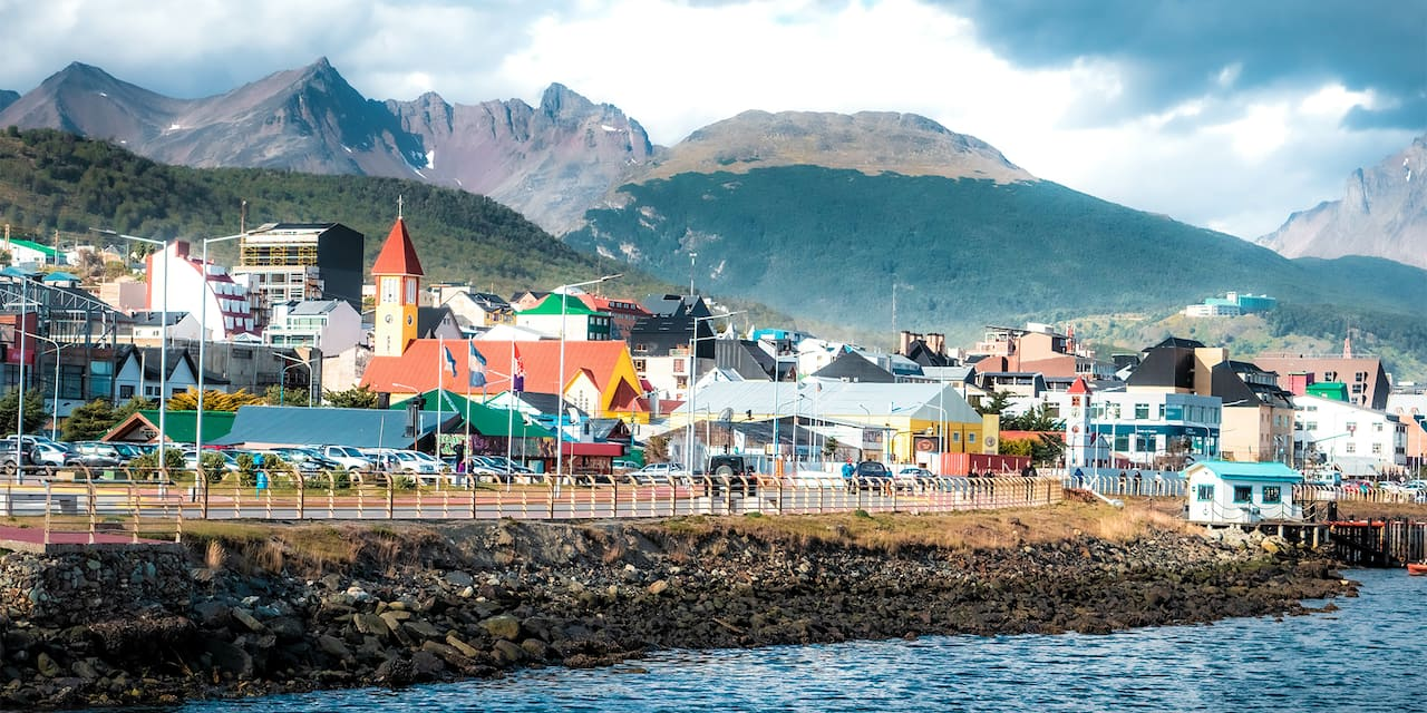 Seaside town of Ushuaia with colorful buildings and flags at the base of the Andes Mountain Range
