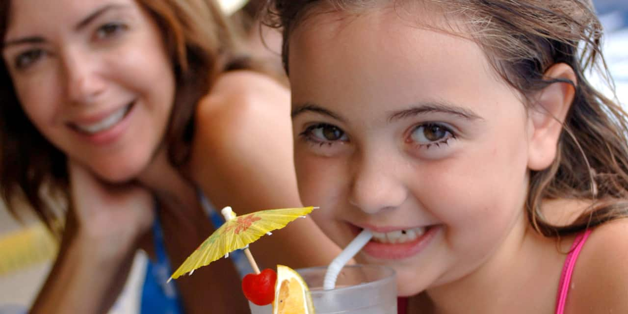 A girl sips an umbrella topped tropical drink with her mom in the background