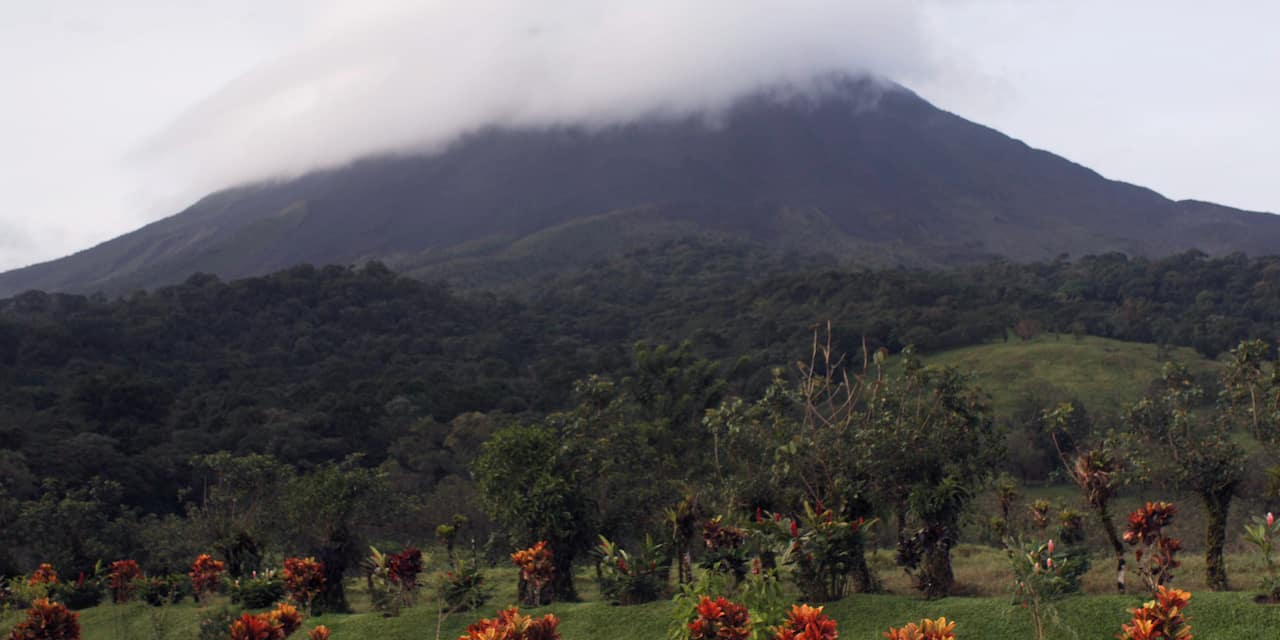 A lush landscape of grass and trees leads up to the cloud-covered Arenal Volcano in Arenal, Costa Rica