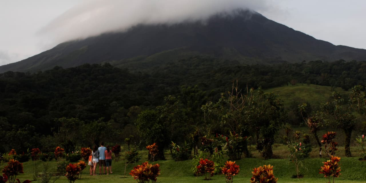 A family of 4 stand in the grass amongst trees looking out at a cloud-covered Arenal Volcano