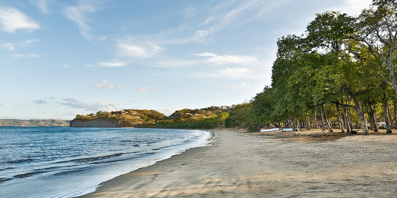 The calm waters and tree lined sands of Playa Panama in Guanacaste, Costa Rica