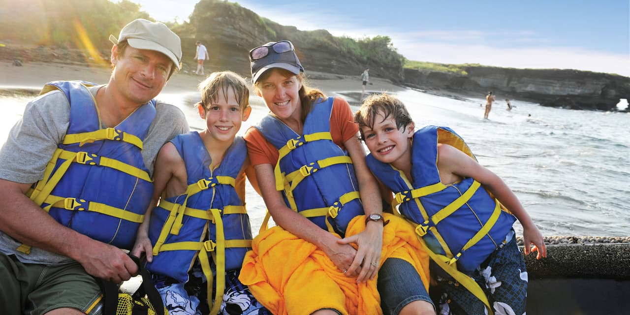 A family of four sitting in front of a beach with lifejackets on