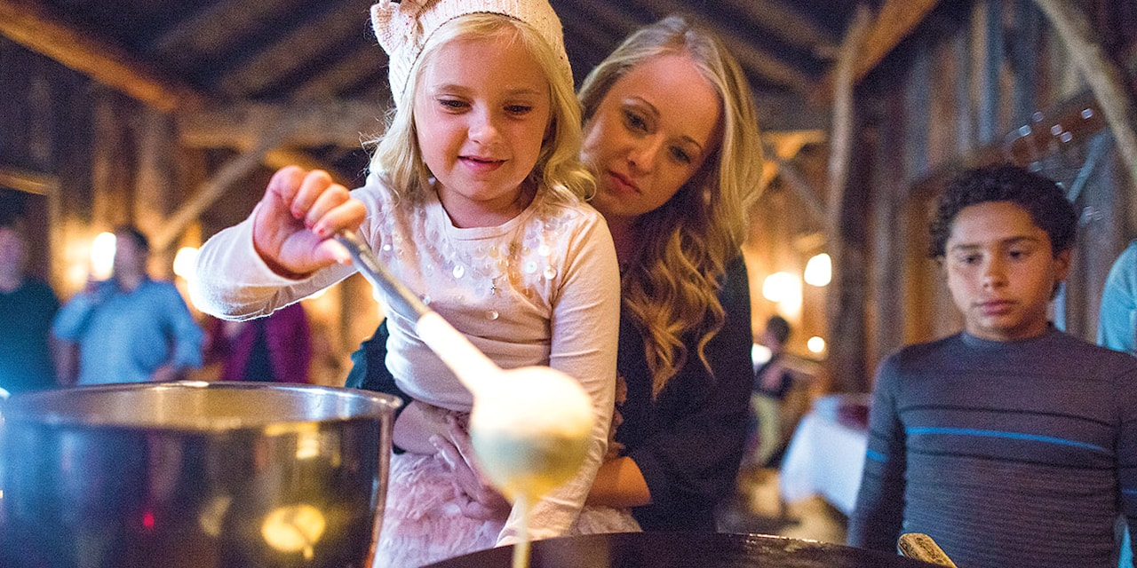 A mother holds her daughter who ladles batter onto a grill