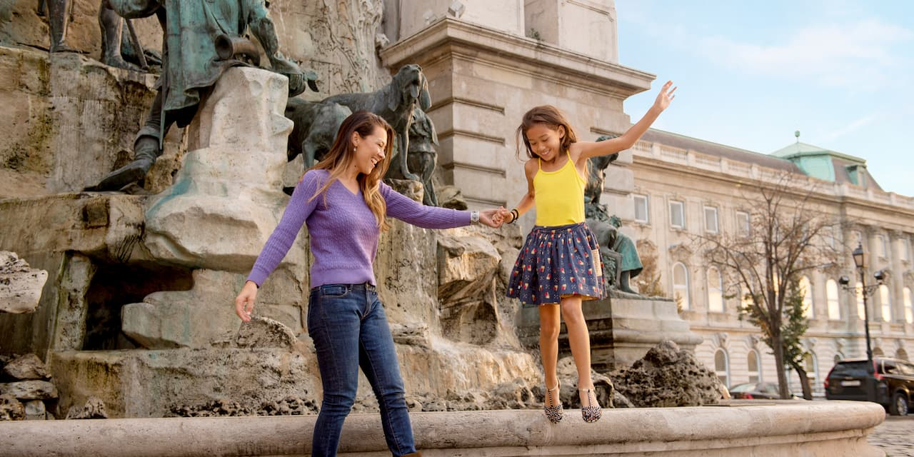 A mother holds her daughter's hand as she jumps off a statue featuring a dog in front of Buda Castle in Budapest, Hungary