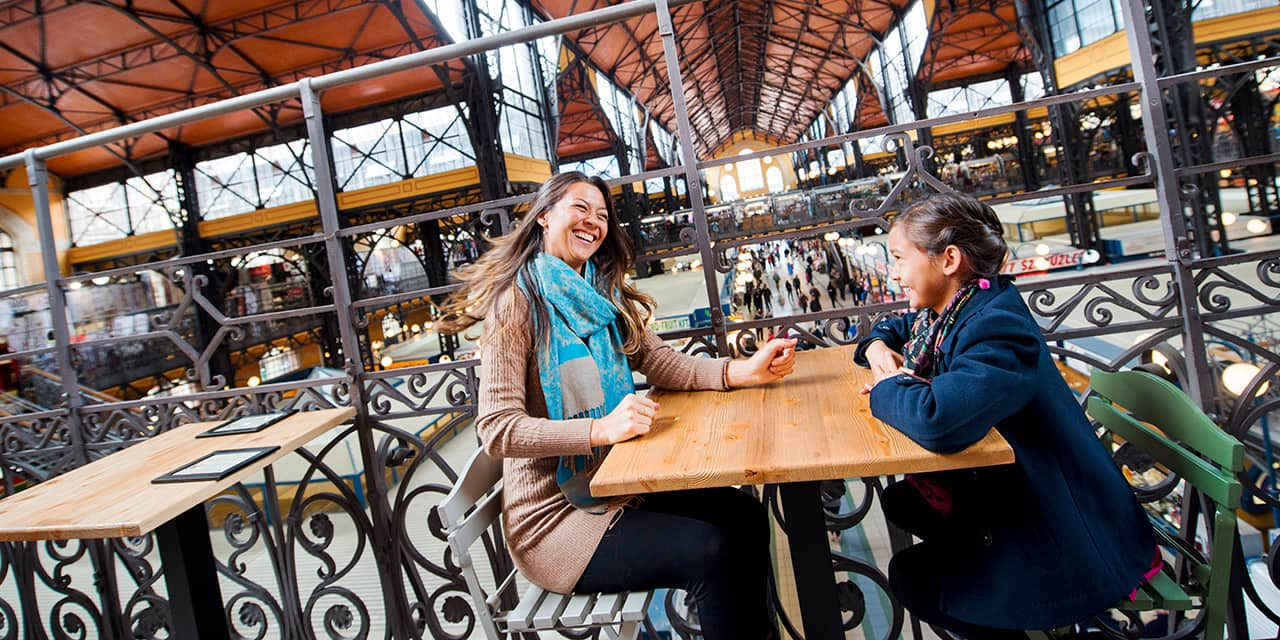 A mother and daughter sit at a table and share a laugh in Budapest's Great Market Hall