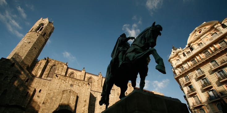 A monument of a king riding his horse surrounded by buildings