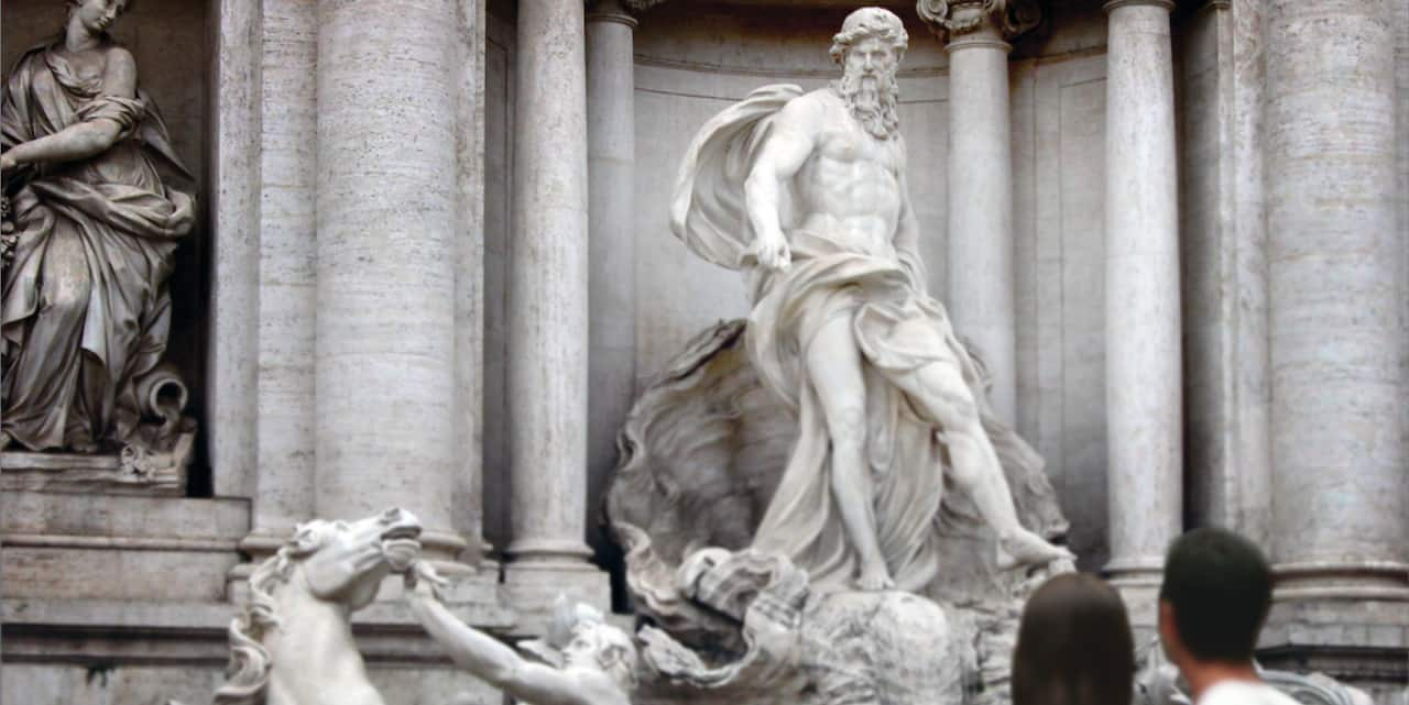 A couple stand in front of the statue of Oceanus in Rome's famed Trevi Fountain