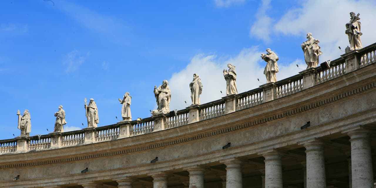 Statues stand atop the colonnades of St. Peter's Basilica in Vatican City