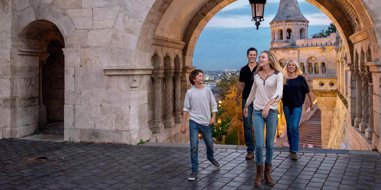 A family of 4 walks through a stone archway into a cobblestone courtyard of an old building