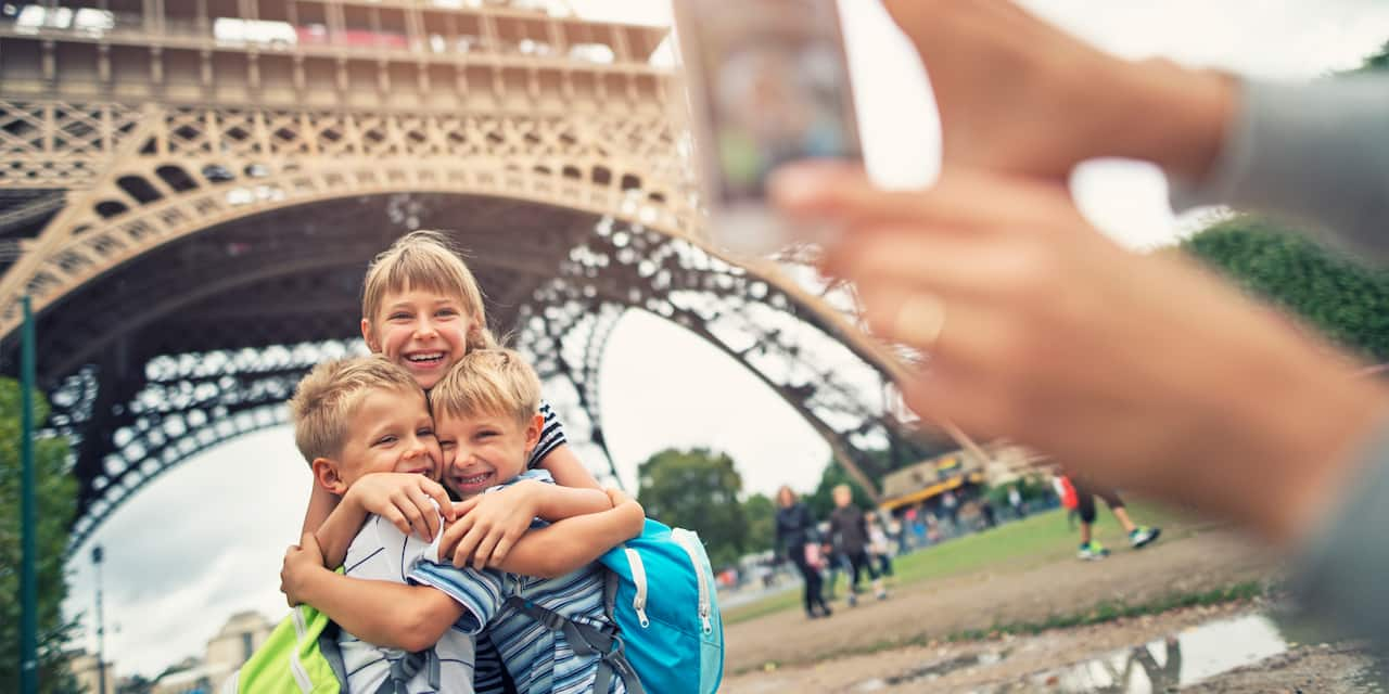 Three kids pose for a picture in front the Eiffel Tower in Paris
