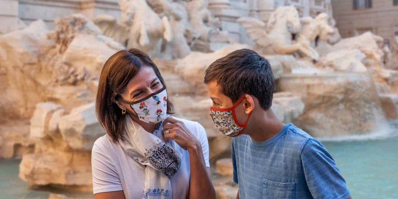 Mother and son wearing masks sitting in front of the Trevi Fountain in Rome