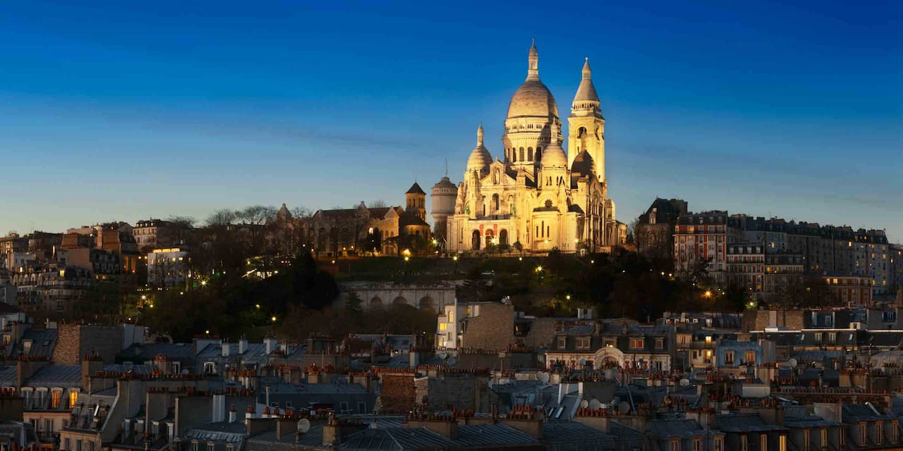 The Basilica of the Sacré Cœur is lit up high on Montmartre at dusk