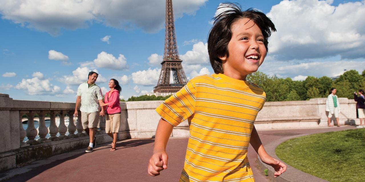 A little boy runs and his parents walk along a path near the Eiffel Tower