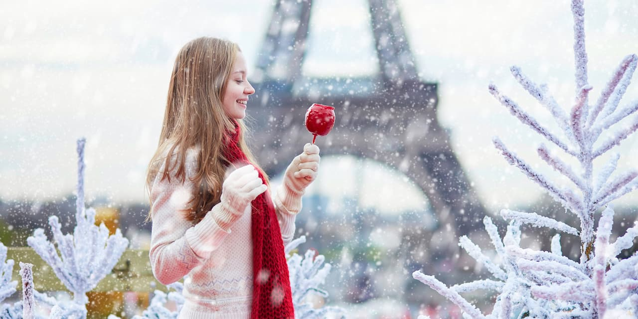A girl dressed in a winter sweater, gloves and scarf, holds a candy apple while standing in front of the Eiffel Tower during a snowfall