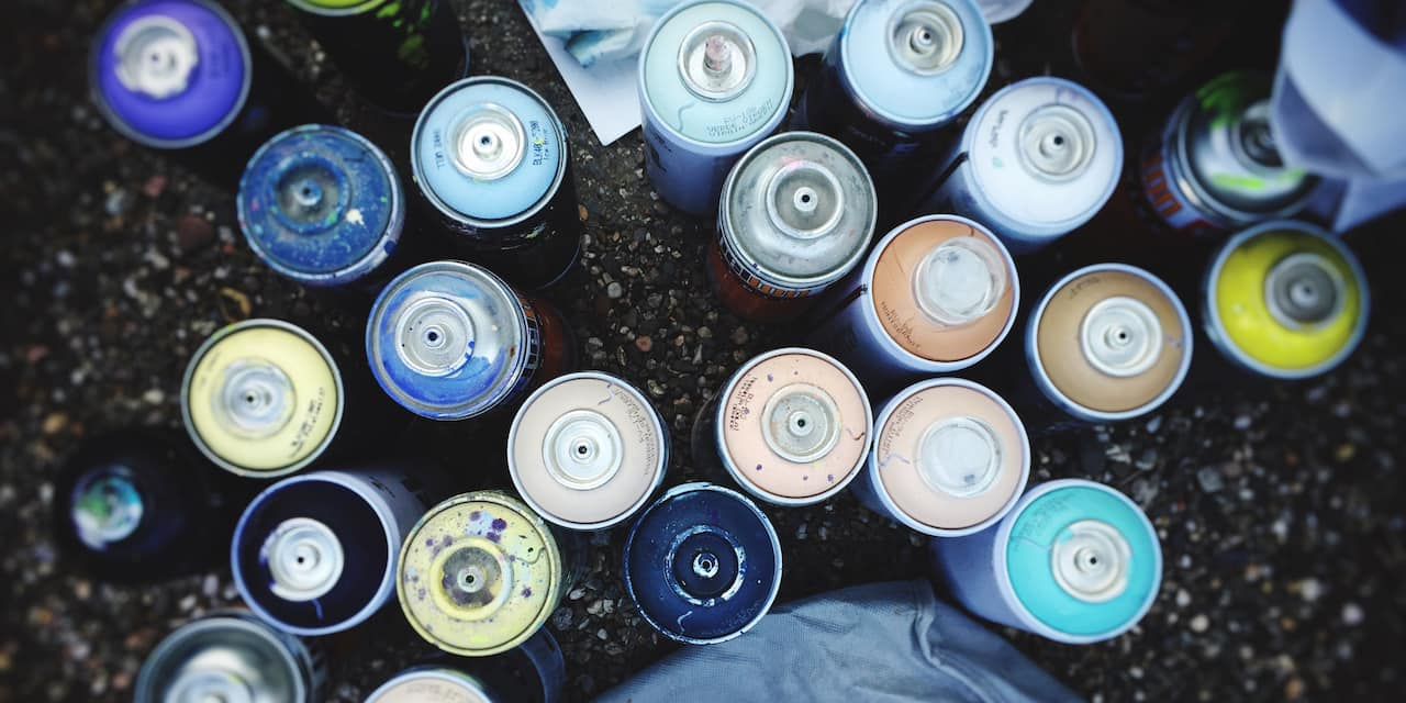 A birds-eye view of a variety of uncapped spray paint cans