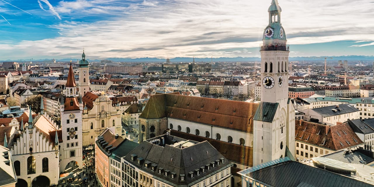 The city of Munich with a tall, spired clock tower standing against a bright, but cloudy sky