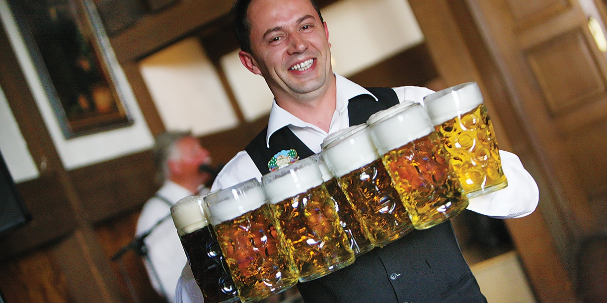 A smiling man holds seven large steins of beer