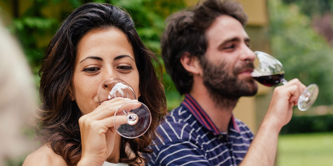 A man and woman drink from their glasses of wine