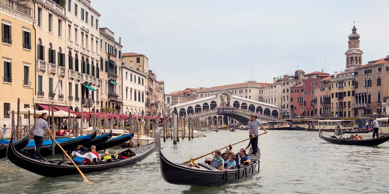 Gondoliers steer several gondolas filled with people on a canal in Venice, Italy