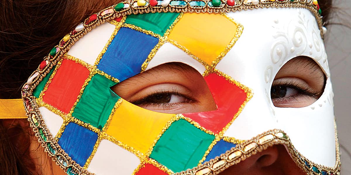 Person wearing a mask decorated with a multicolor ribbon border and diamonds on one side