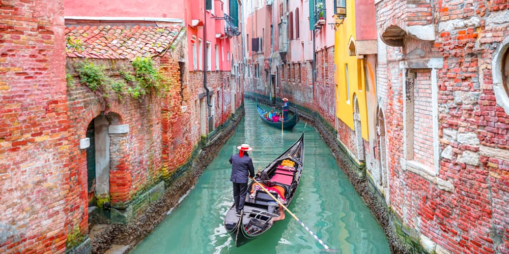 Gondoliers steer gondolas in a canal in Venice
