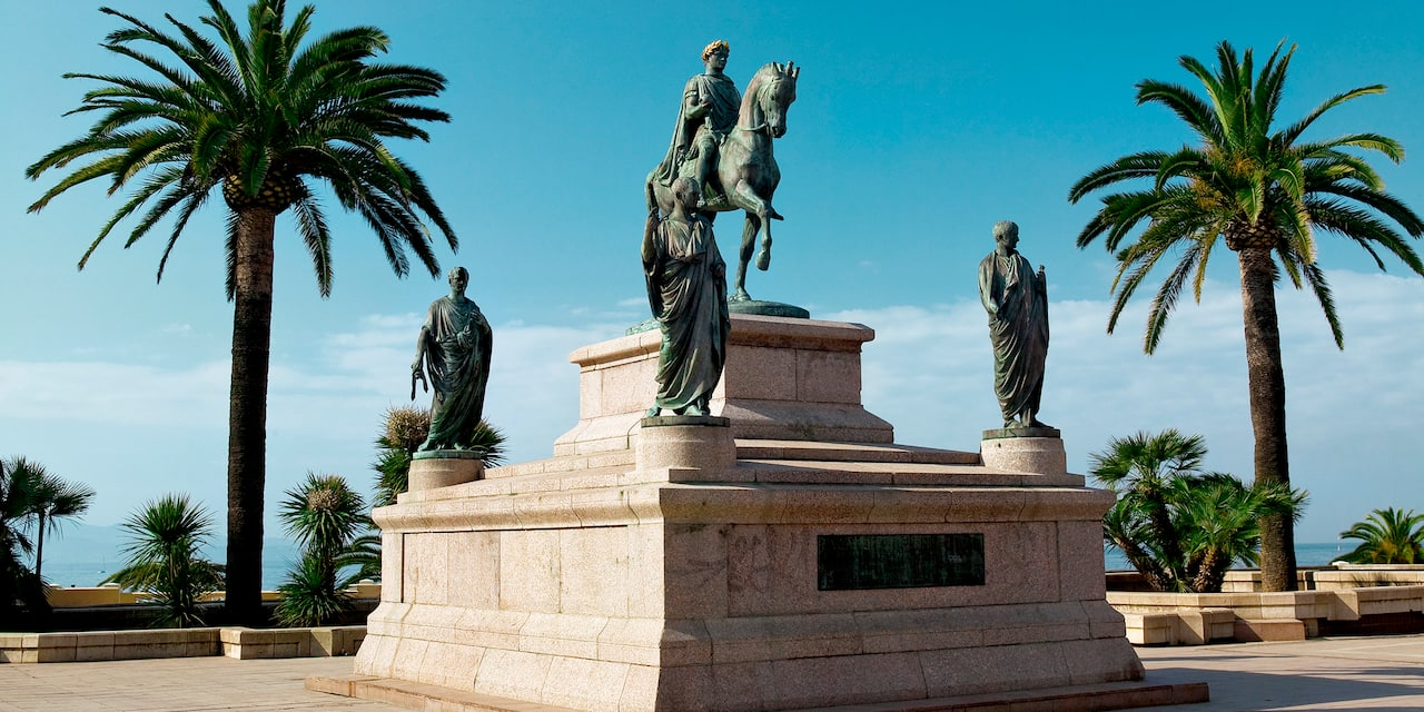 The statue of Napoleon Bonaparte on horseback and his 4 brothers stands between 2 palm trees