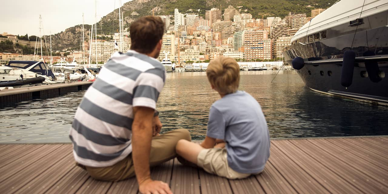 A father and son sit on a marina dock looking across the water at the a city that sits at the base of a mountain